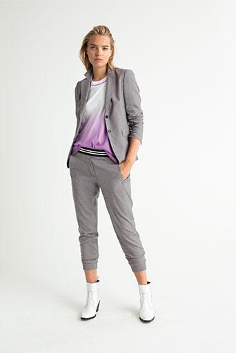 Junge Frau in grauem Anzug, weiß-pinkem Shirt und weißen Stiefeln