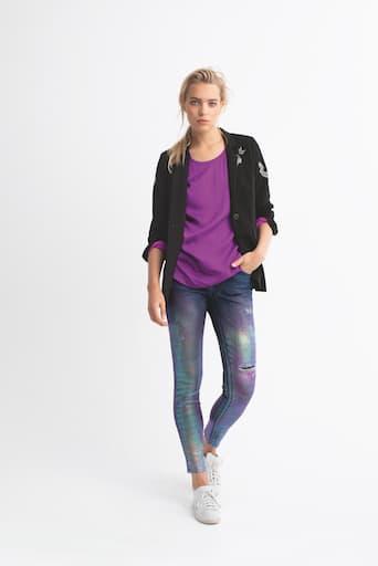 Blondes Model in Jeans mit lila Galaxie-Muster, violettem Shirt und schwarzer Jacke