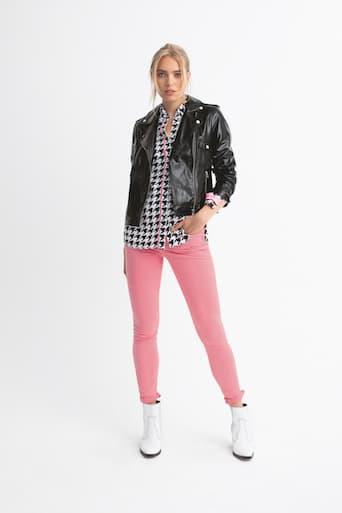 Blondes Model in pinken Hosen, weißen Stiefeln und schwarzer Lederjacke