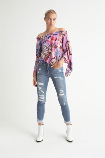 Blondes Model in Jeans, weißen Stiefeln und farbigem top