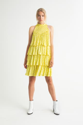 Blondes Model in gelbem Kleid und weißen Stiefeln